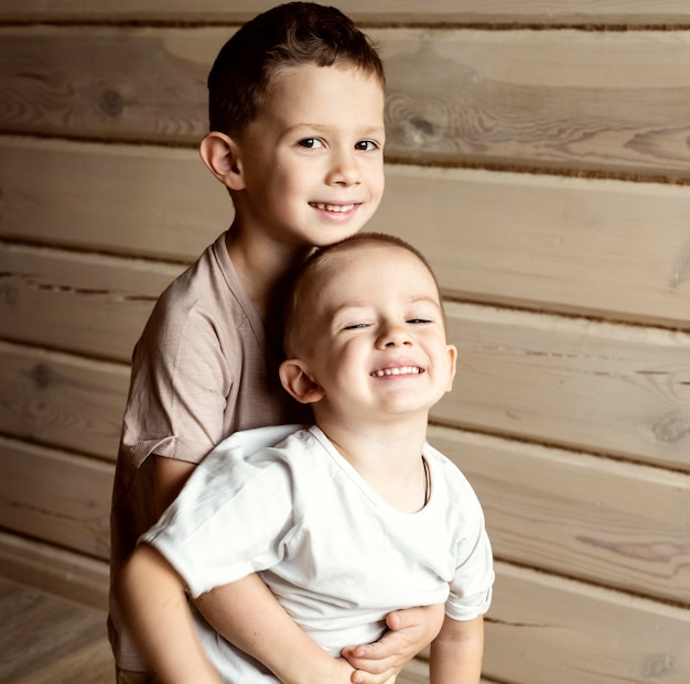 Мальчик обнимает своего младшего брата. старший брат держит младшего на руках