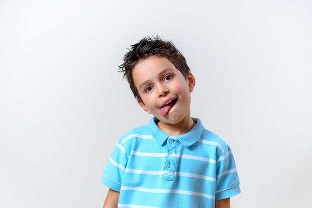 Мальчик в синей футболке склонился над головой и высунул язык.