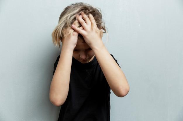 恐怖の少年は両手で頭を抱えています。灰色の背景。ストレスと抑圧。
