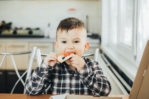 집에서 부엌에서 소년 연어와 피자를 먹고