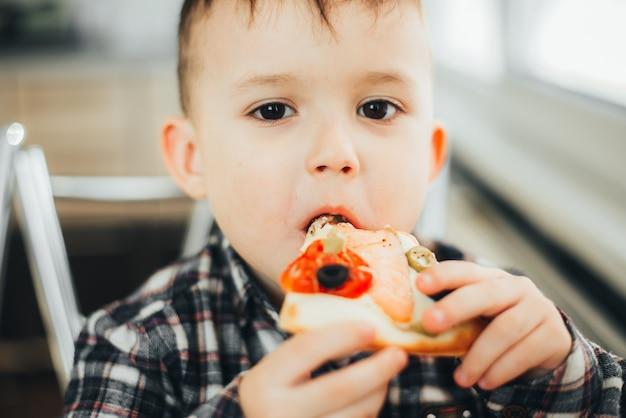 Мальчик на кухне дома ест пиццу с лососем