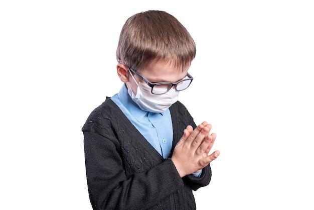 가면을 쓴 소년이 기도하고 있습니다. 흰색 배경에 고립. 고품질 사진