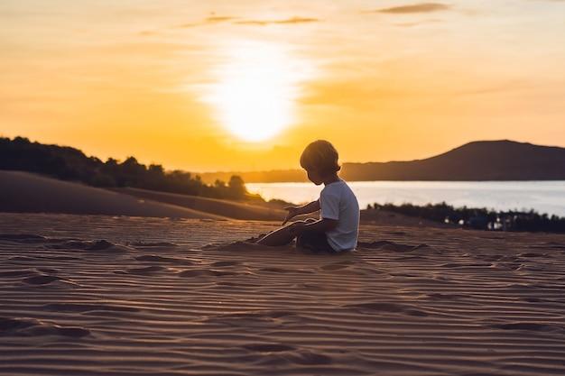 새벽에 붉은 사막의 소년. 어린이 개념으로 여행.
