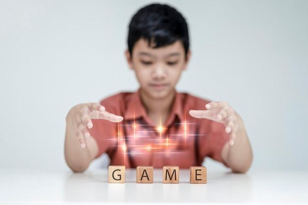 Мальчик закидывает магию в игру-куб, маленький забавный волшебник с деревянным кубиком, концепт, мальчик-стример радуется победе, профессиональный геймер играет в онлайн-игры.