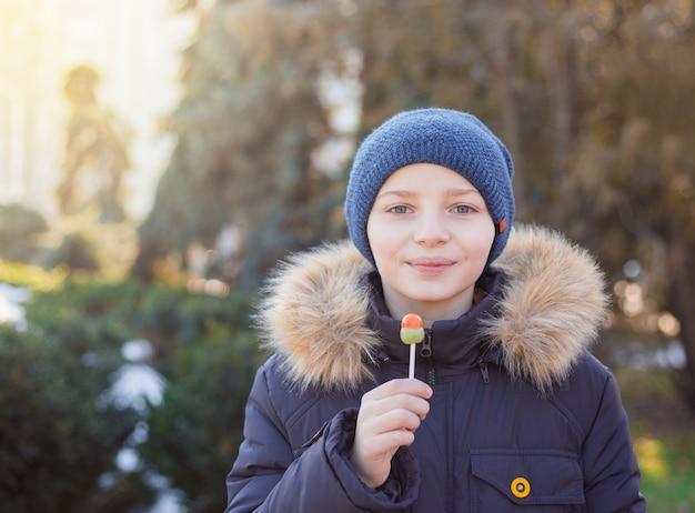 Мальчик ест вкусный леденец, холодное время года
