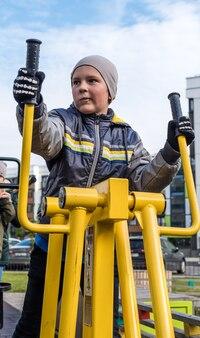 소년은 야외에서 거리 운동 기계에 종사하고 있습니다.