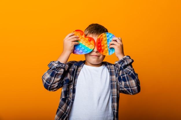 Мальчик держит в руках сенсорные хлопающие игрушки. push-игра. счастливый мальчик с поп-это
