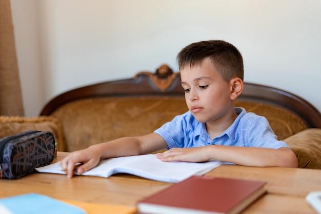 그 소년은 학교 과제로 돌아가기를 별로 좋아하지 않고 공책 위에 앉아 어려운 과제를 해결합니다.