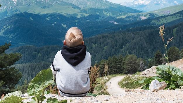 소년은 앉아서 코카서스 산맥의 풍경을 바라보고 있습니다. 야외 여행 현지 여행