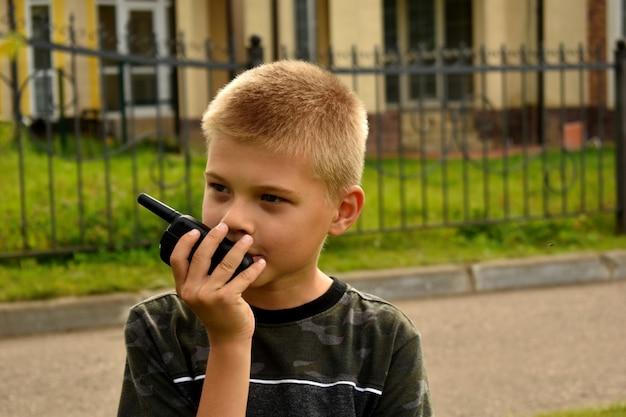 その少年はトランシーバーで話している。ボーイッシュな戦争ゲーム。