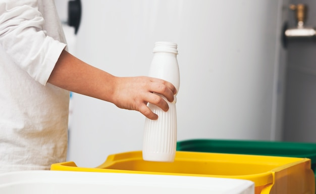 Мальчик выбрасывает пустую пластиковую бутылку в одну из трех урн для мусора.