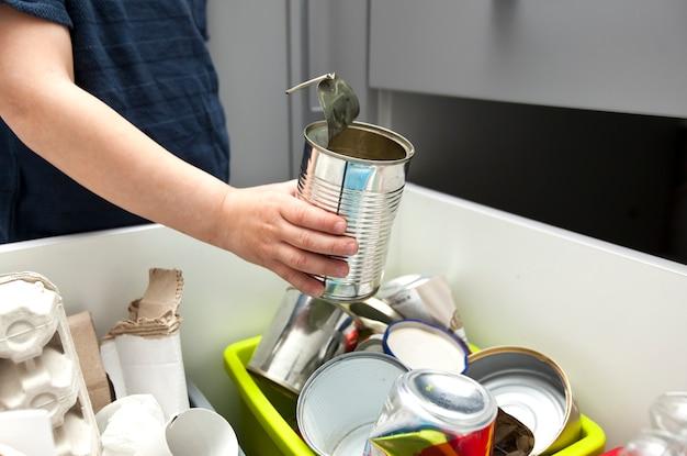 Мальчик выбрасывает мусор в один из четырех контейнеров для сортировки мусора.