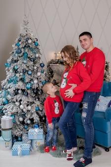 Мальчик целует живот беременной мамы во время празднования нового года happy new year