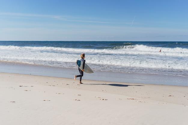 少年はサーフィンの前にビーチで練習をし、サーフボードで水に流れ込む