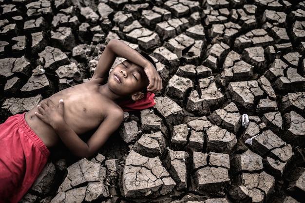 소년은 평평하게 누워 손을 뱃속에 놓고 이마를 마른 토양에 눕습니다.
