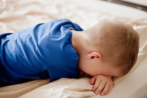 Мальчик лежит на кровати с повернутой спиной и плачет.