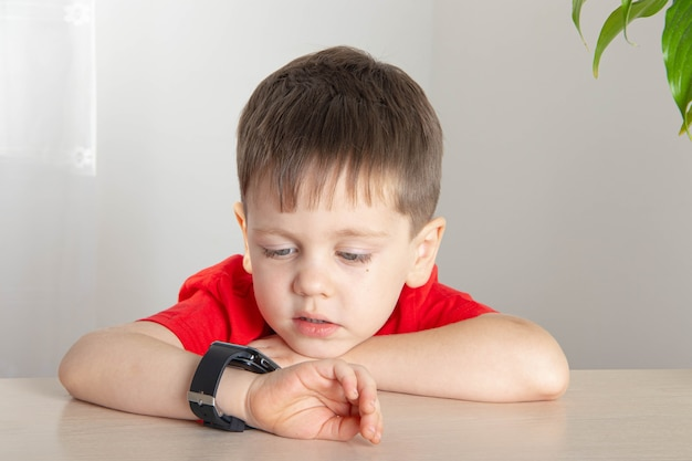 少年は時計の時刻を見ます。子供がテーブルに座っています。時間についての記事。コースの終わり。