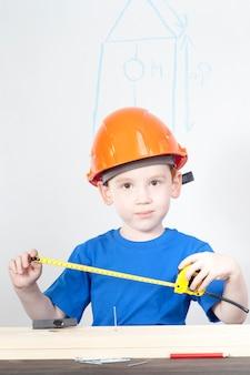 Мальчик делает мерки для постройки скворечника, уроки труда.