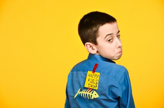 Мальчик на желтом фоне в синей рубашке с рыбой приклеил скотч и лист бумаги на спине