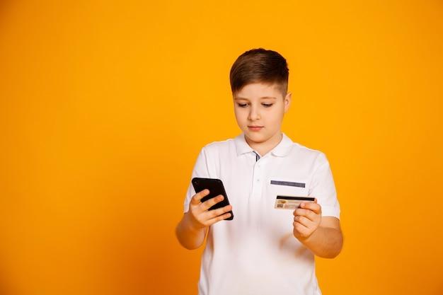 男の子はクレジットカードとスマートフォンを持っているクレジットカードの男の子で支払います