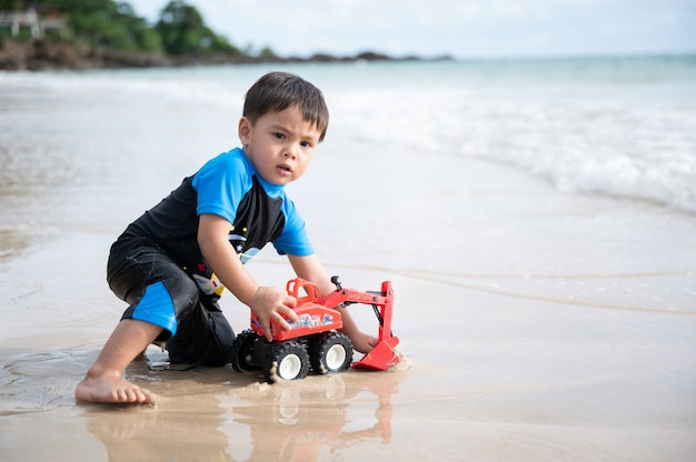 少年はビーチで掘削機のおもちゃを再生します