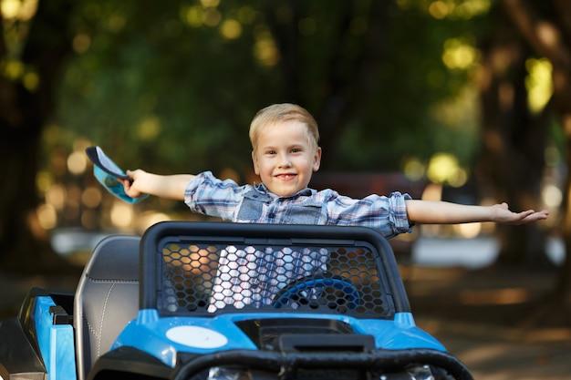 소년 연극은 큰 기계 장난감 트럭을 운전하는 모자에 백인 외모의 귀여운 어린 소년 공원에서 자동차를 운전