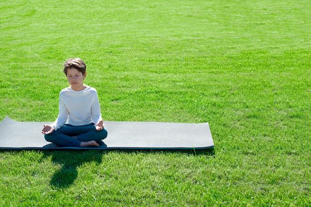 Мальчик занимается йогой на траве. активный отдых для детей
