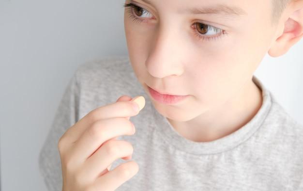 少年は錠剤を口に入れます。クローズアップ写真