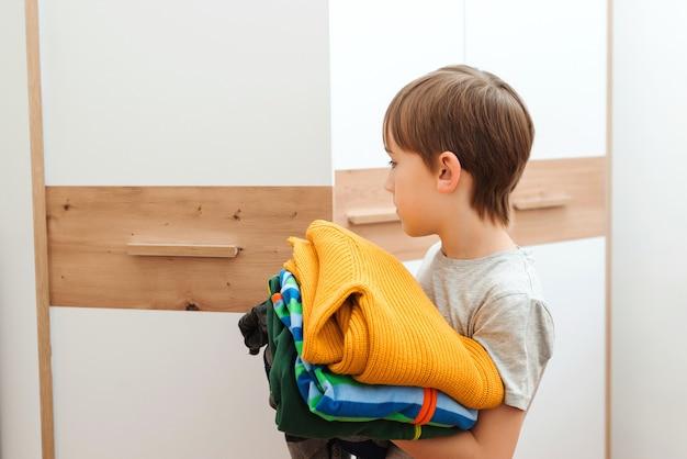 Мальчик наводит порядок в шкафу. стопка разноцветной одежды. малыш организовывает одежду в шкафу.