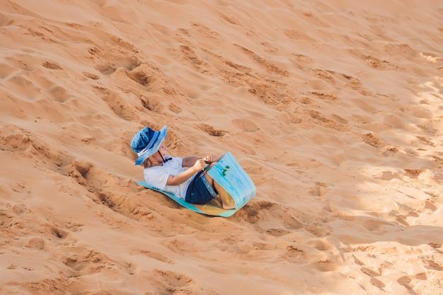 소년은 새벽에 붉은 사막을 돌아 다닌다. 어린이 개념 소란 여행.