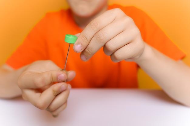 手前の男の子の手は、クイリングツールと薄い色の紙片を持っています