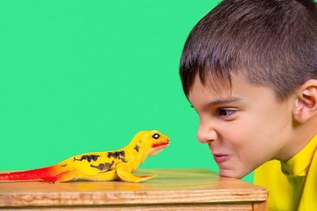 노란 셔츠를 입은 소년은 테이블에 턱을 대고 공룡 장난감을 열심히 보고 있다