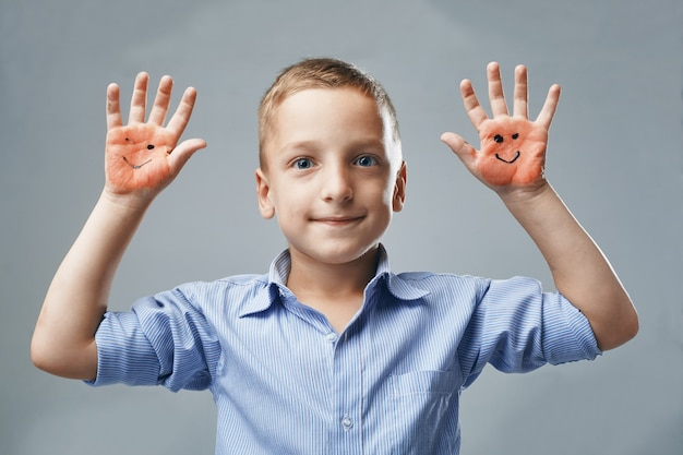 소년은 그려진 이모티콘으로 손을 보여줍니다.