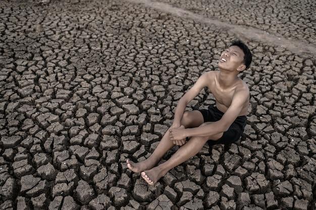소년은 무릎을 굽히고 하늘을 보면서 마른 토양에 비를 요구합니다.