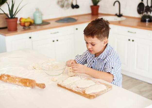 少年は台所のテーブルに座って、生地から何かを彫刻します。