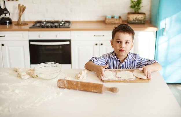男の子は台所のテーブルに座って、目の前に生地を置いています