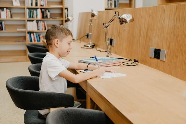 소년은 도서관에 앉아서 탁자에 있는 공책에 글을 씁니다. 숙제를 준비합니다. 좋은 학생. 남학생은 공부하는 것을 좋아합니다. 학교의 여유 공간.