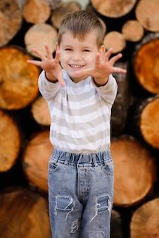 소년은 미소를 짓고 뻗은 팔을 보여줍니다. 행복한 어린 시절의 개념