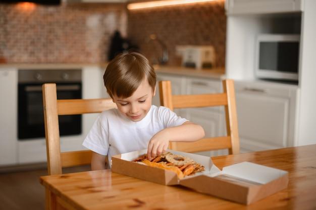少年は笑顔で、キッチンに座っているボックスでドライフルーツを並べ替えます