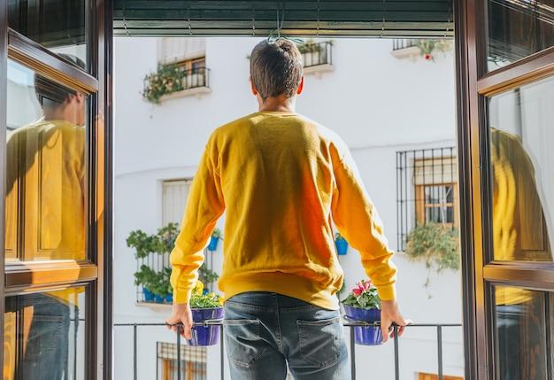 Мальчик стоит на балконе с видом на улицу из горшечных окон в желтой кофте