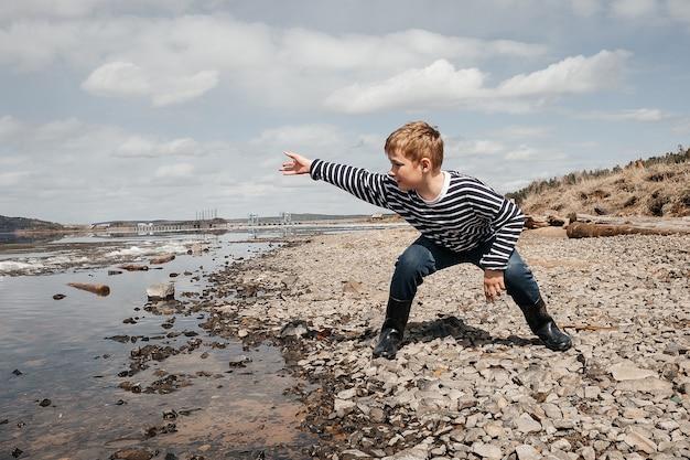 소년은 물에 돌을 던졌습니다. 조끼를 입은 쾌활한 소년이 강둑에서 놀고 있습니다.