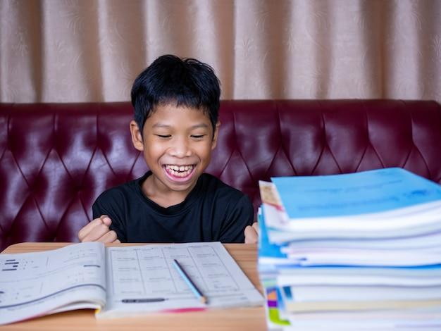 Мальчик был очень счастлив закончить домашнее задание. он сидел на деревянном столе, а рядом лежала стопка книг. фоном служит красный диван и кремовые шторы.