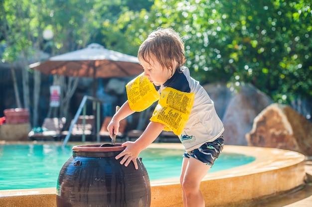 少年はプールの周りの砂の足を洗う