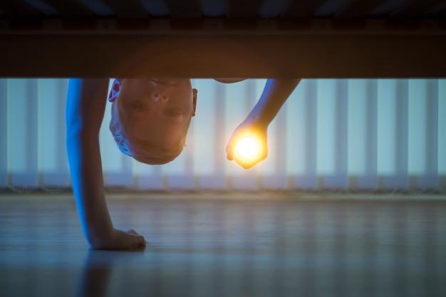 침대 밑에 손전등을 든 소년. 밤 시간