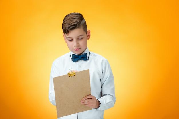 ノートのためのペンとタブレットを持つ少年