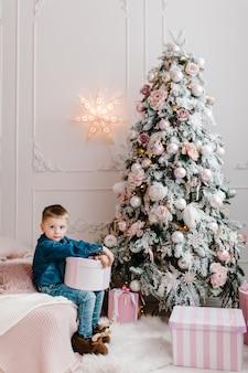 Мальчик с подарками возле елки с новым годом и рождеством