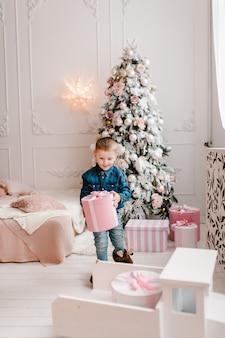 Мальчик с подарками возле елки концепция семейного зимнего отдыха