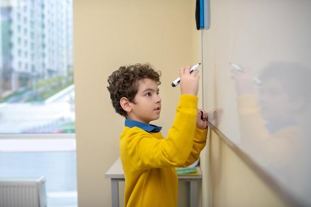 Мальчик пишет на доске маркером