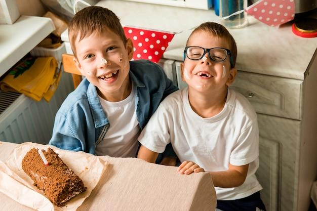 男の子たちは誕生日を祝っています。子供の誕生日の道具。兄弟たちは顔をケーキで覆った。自宅での家族のお祝い