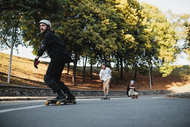 男の子たちはトリックをして乗ります。夕方の暖かい街のスケートボードで。高品質の写真